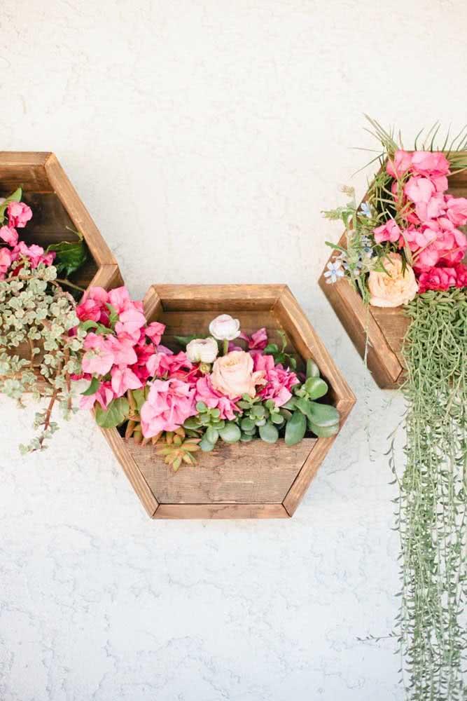 Floreira de parede de madeira em formato hexagonal e decorada com flores de corte