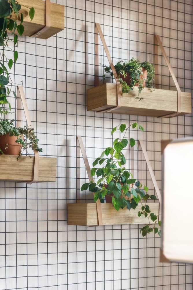 As alças de couro são o destaque dessas floreiras de madeira de parede