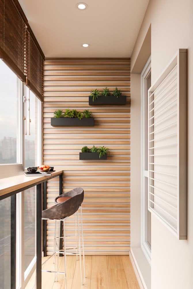 A varanda clean e moderna do apartamento ganhou floreiras no mesmo estilo