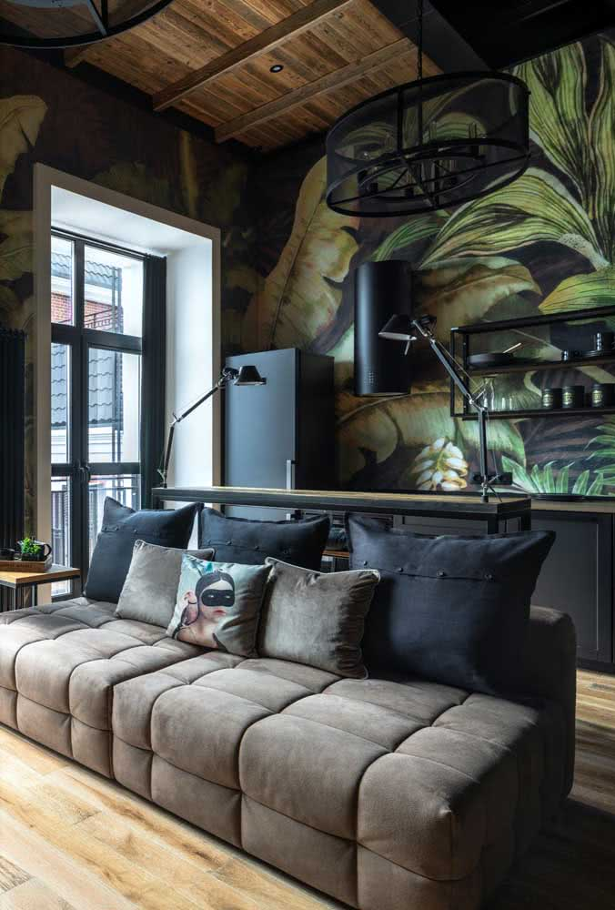 Já a sala integrada e moderna trouxe um sofá de três lugares marrom e almofadas pretas para combinar
