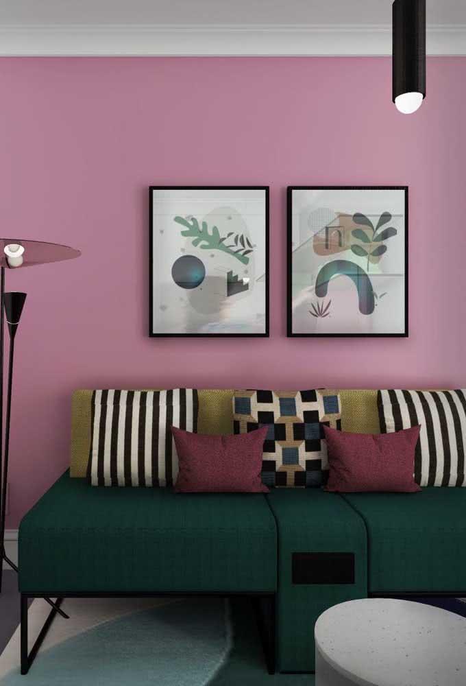 Parede rosa e sofá verde: decoração criativa para sala pequena