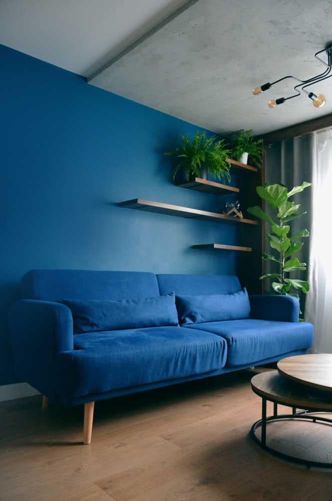 Apostar em parede e sofá na mesma cor é um truque interessante para uniformizar e ampliar visualmente o espaço