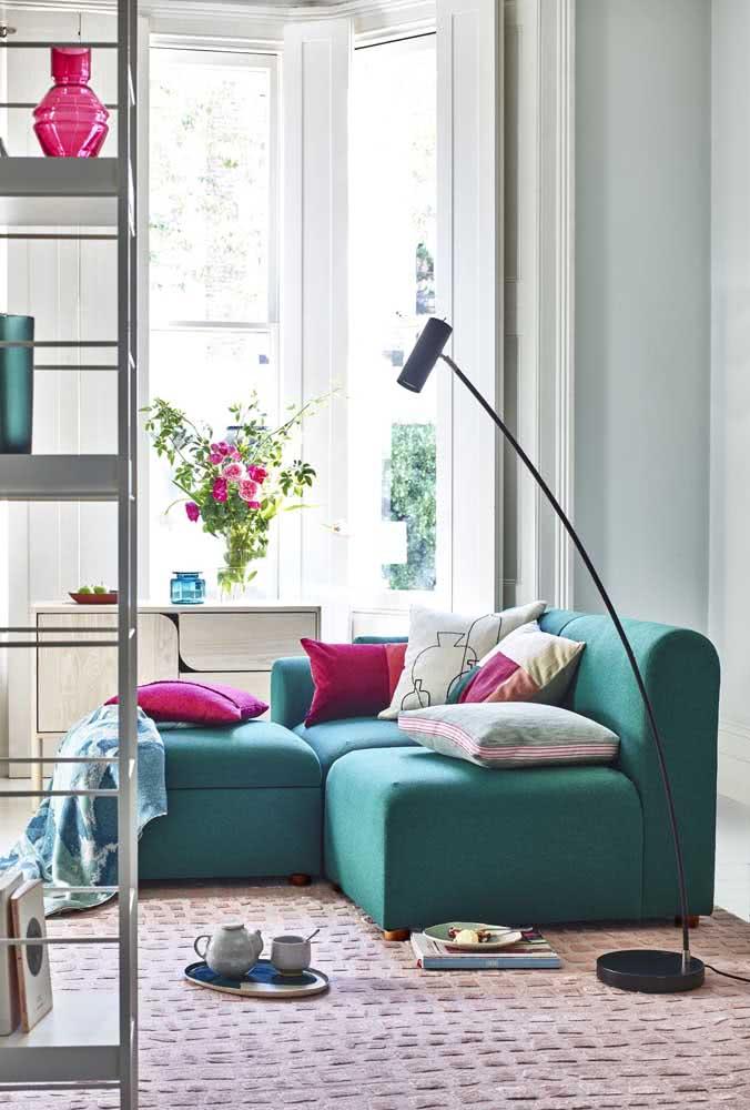 Mas se é de cor que você gosta, então se joga no sofá verde de veludo decorado com almofadas cor de rosa