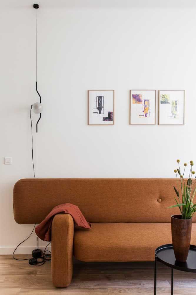 Sofá marrom de design clean e moderno contrastando com a parede branca da sala
