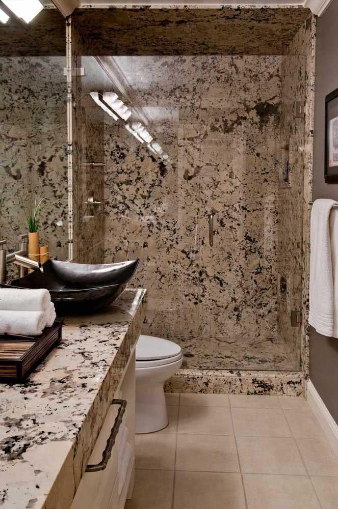 Já nesse banheiro, o mesmo granito utilizado para bancada reveste a área do box