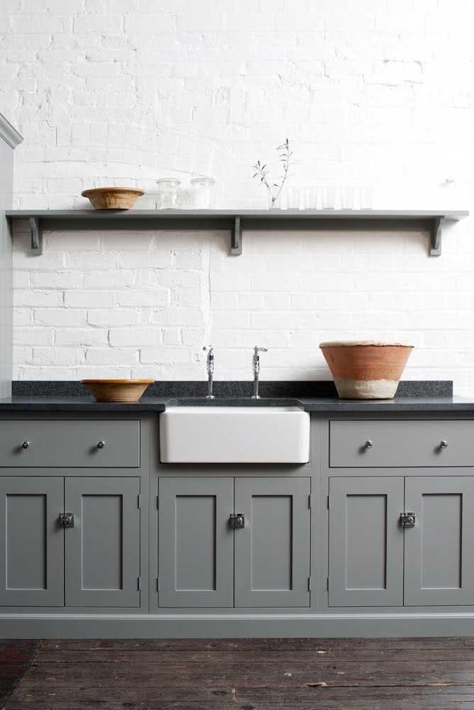Essa cozinha que passeia pelo rústico e o moderno traz uma bancada de granito preto combinando com a prateleira