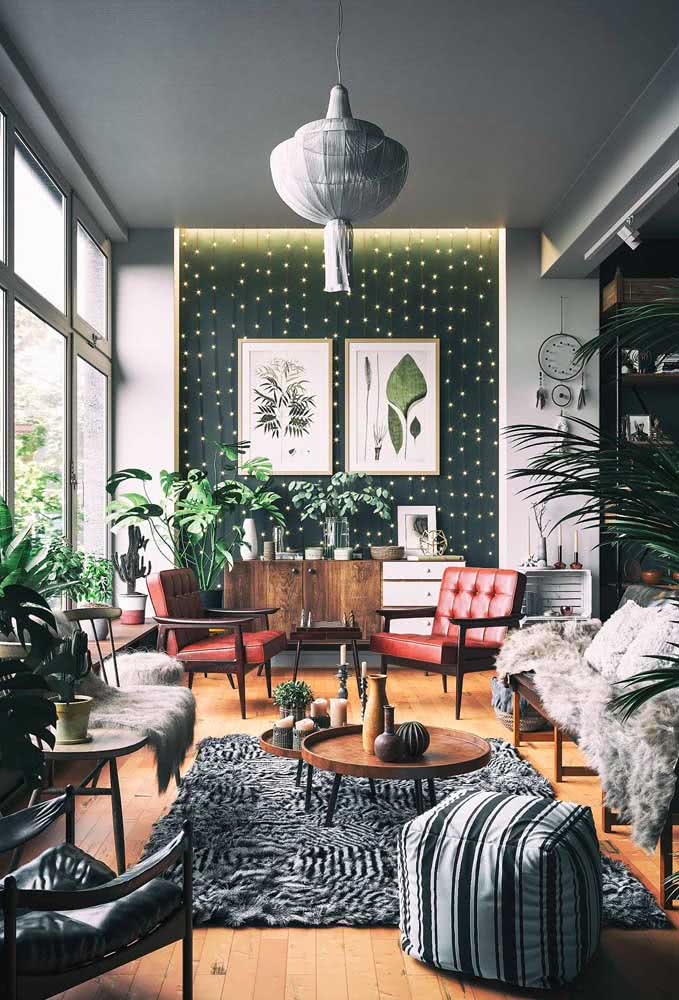 Objetos de decoração boho incluem tapete, almofadas, plantas, luzes e macramê