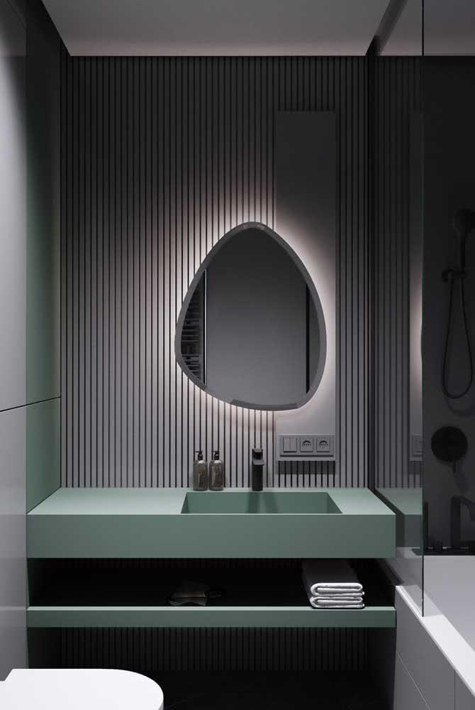Painel ripado cinza para o banheiro. Destaque para a iluminação atrás do espelho que valoriza todo o conjunto