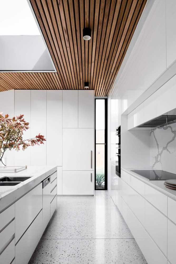 A cozinha branca ficou mais charmosa e acolhedora com o painel ripado no teto