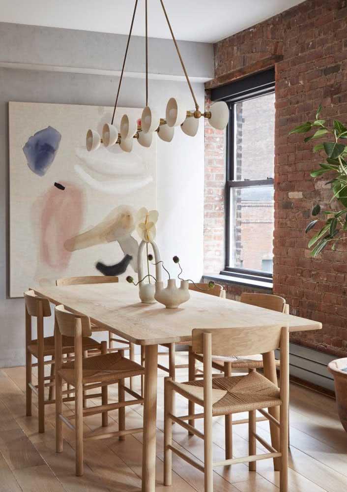 Sala de jantar com parede de tijolinhos e outra parede com concreto aparente.