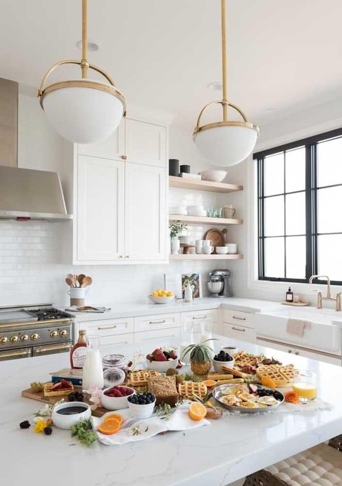 Mesa de café da manhã servido na cozinha. As frutas decoram e integram o menu