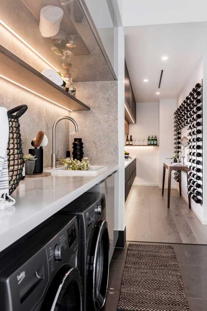 Já aqui, as prateleiras ajudam a organizar a lavanderia integrada com a cozinha