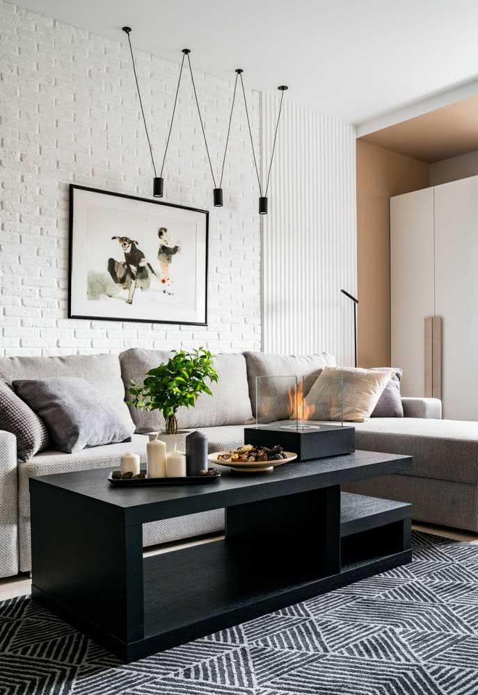 Sala com tijolinho branco na parede da TV. Os quadros e a luminária completam o ambiente