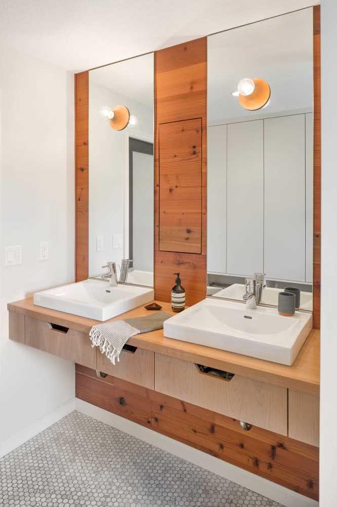 Nesse outro banheiro o charme da madeira aparece no painel atrás da bancada