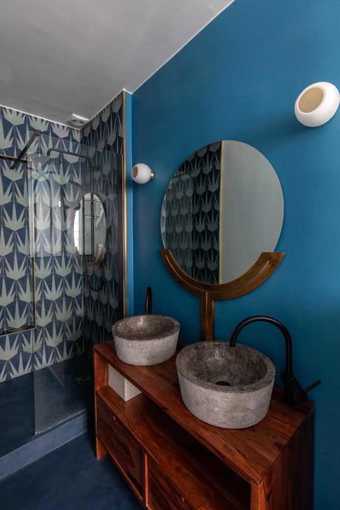 Já aqui, o banheiro moderno azul ganhou o contraste do antigo móvel de madeira maciça