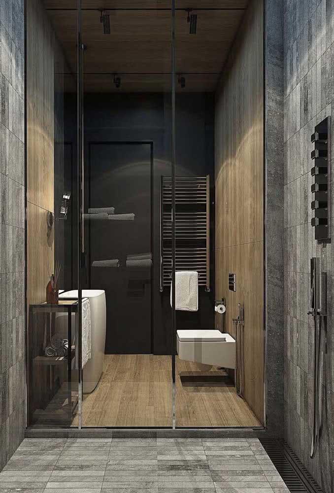 Banheiro amadeirado com cinza e preto. Para fechar a proposta, uma iluminação sob medida