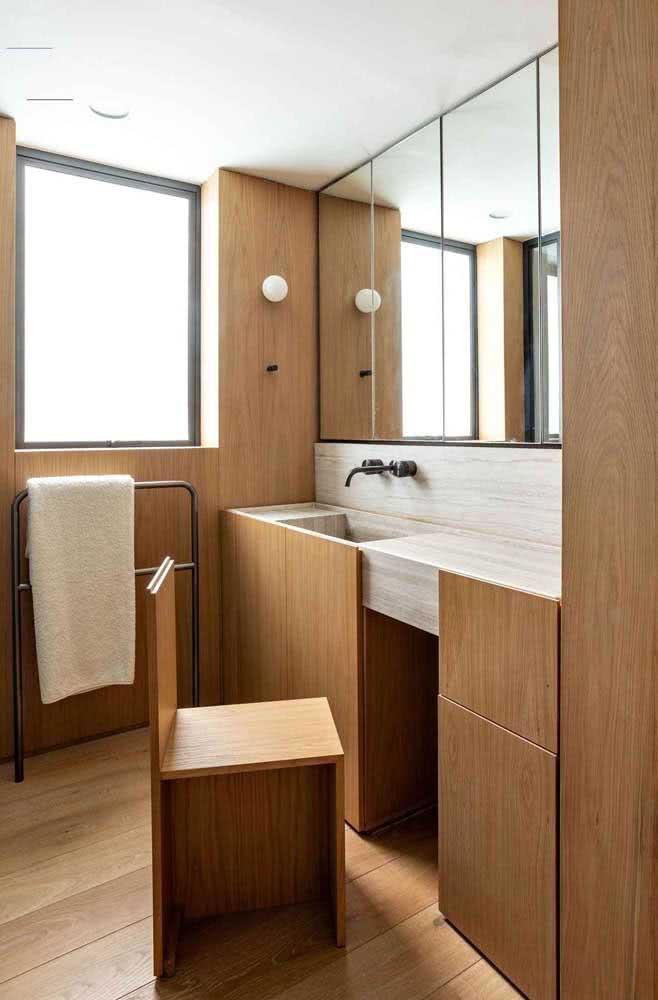 Já por aqui, o revestimento de madeira vai do piso às paredes criando uma uniformidade visual