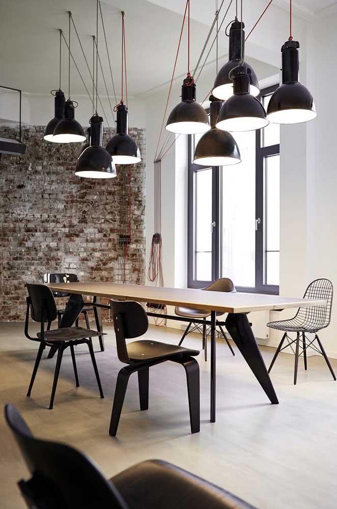 Aqui, a mesa industrial recebeu a companhia de cadeiras de diferentes modelos
