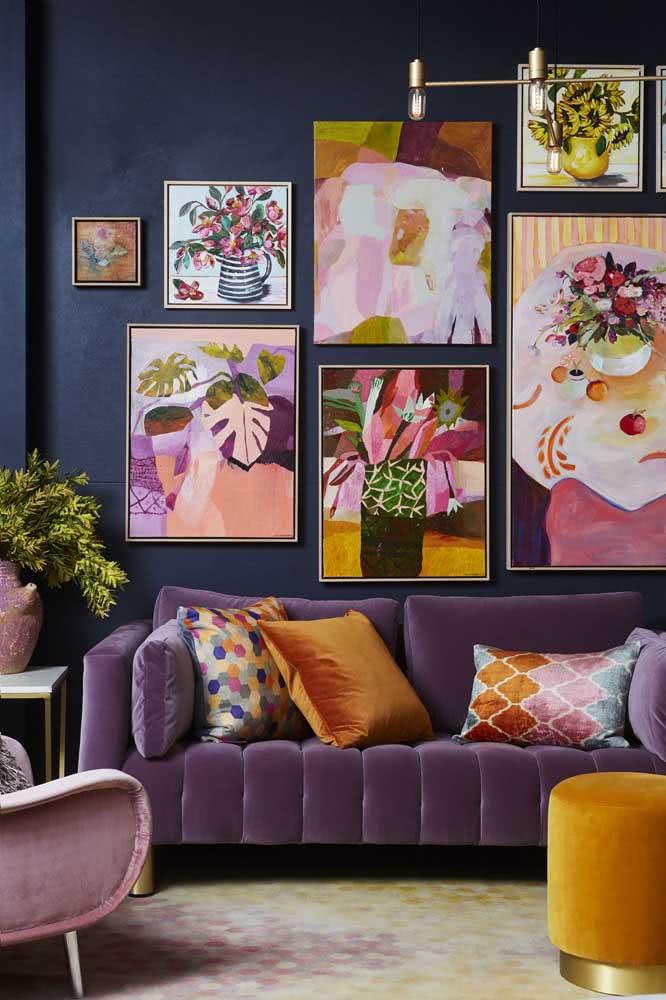 A parede azul petróleo recebeu muito bem a composição de quadros coloridos e contemporâneos