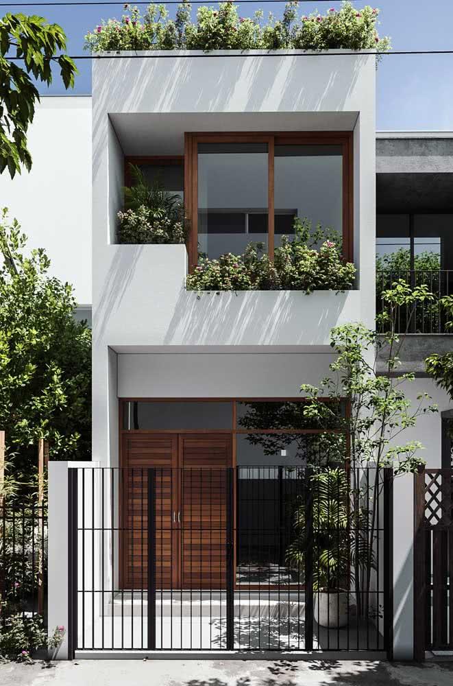 As plantas e a madeira deixam a fachada moderna mais receptiva e acolhedora