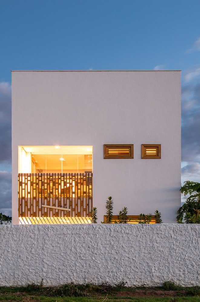 Fachada de casa moderna e minimalista. O grande destaque aqui está na iluminação que valoriza a entrada da residência