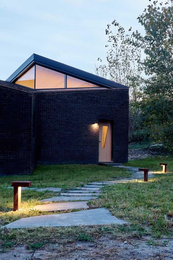 Tijolinhos pretos na fachada da casa moderna. O jardim completa a cena