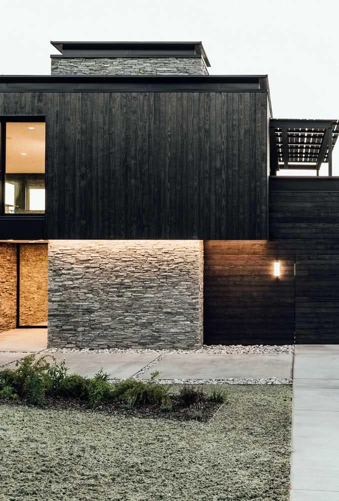 A combinação entre a madeira escura e as pedras rústicas ficou perfeita nessa fachada moderna