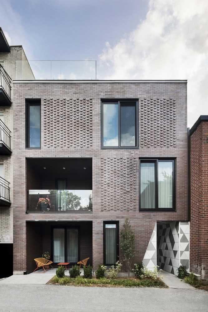 Fachada de casa moderna em tons de cinza com aberturas de luz e ventilação feitas com o próprio tijolinho