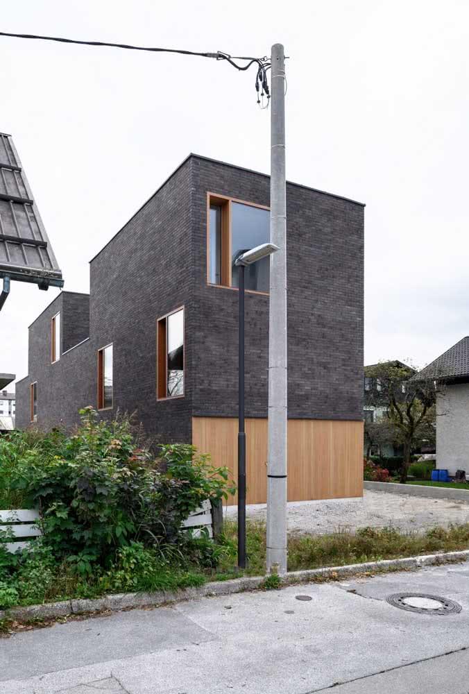 Fachada de casa moderna com três texturas diferentes: madeira, vidro e tijolinhos cinza