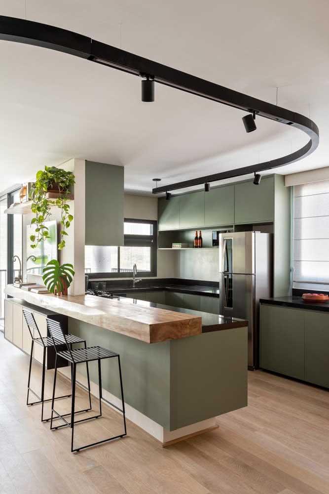 Nessa outra ideia, a bancada suspensa começa na sala como apoio para TV e termina na cozinha como apoio para as refeições. Uma maneira diferente de integrar os ambientes