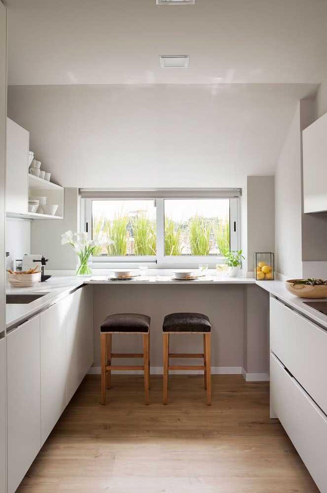 A cozinha em U ficou mais funcional com a bancada suspensa embaixo da janela
