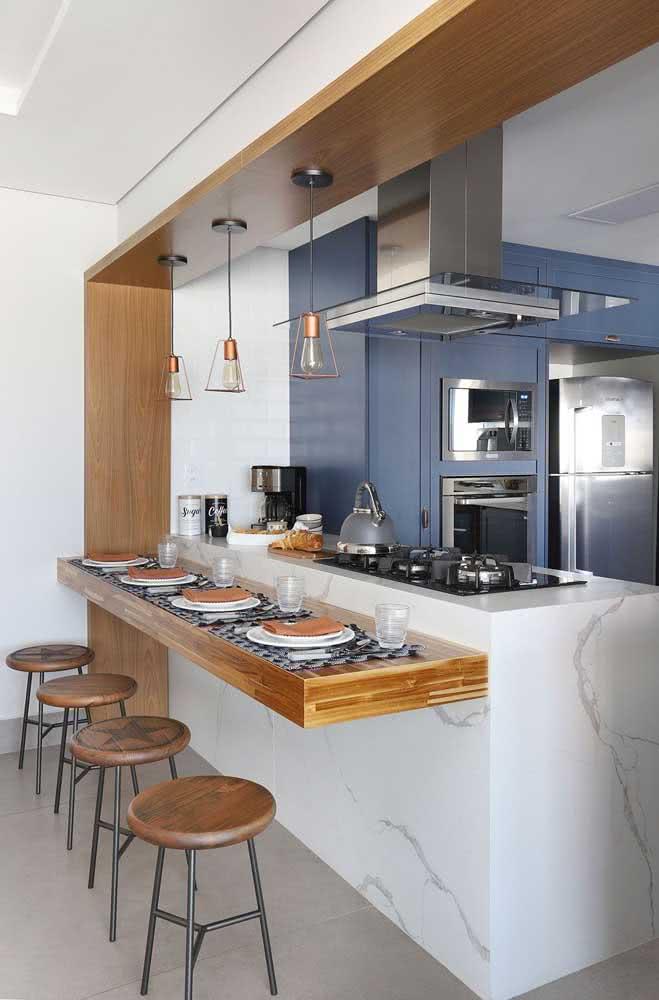 Aqui, a ilha da cozinha em mármore ganhou a companhia de uma linda bancada suspensa de madeira maciça