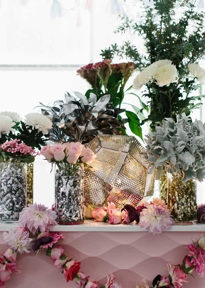 E na mesa principal as flores dividem espaço com o brilho prateado