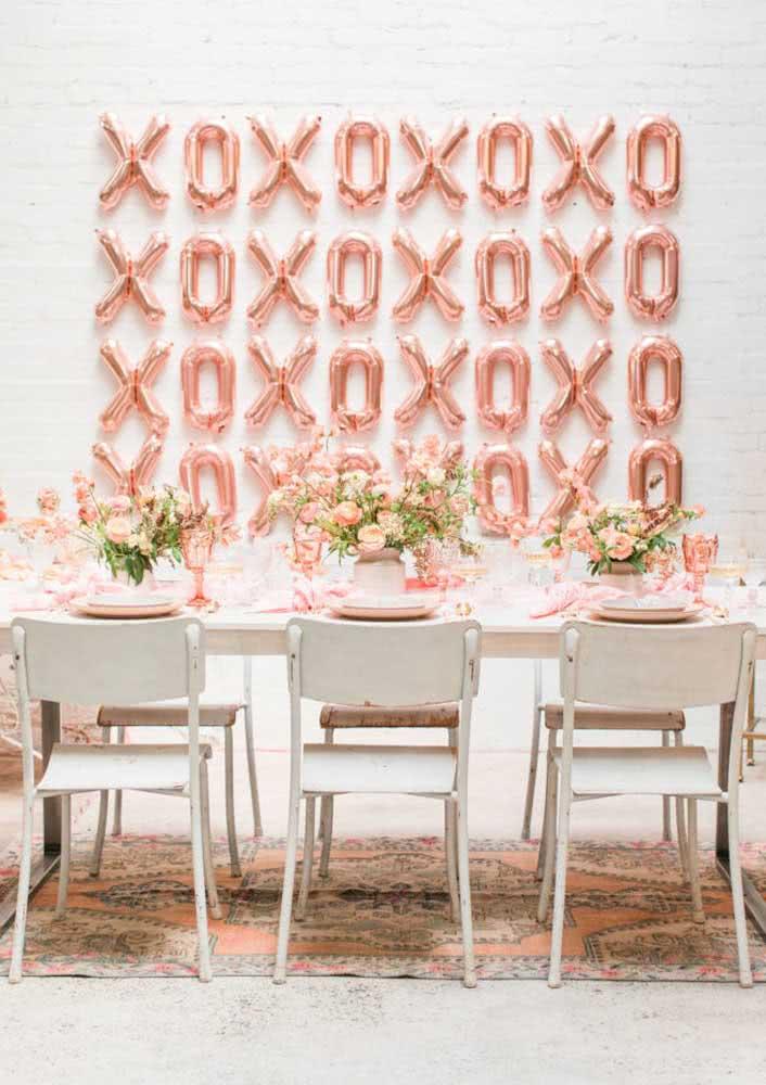 Balões e louças rosé gold para entrar no tema da festa