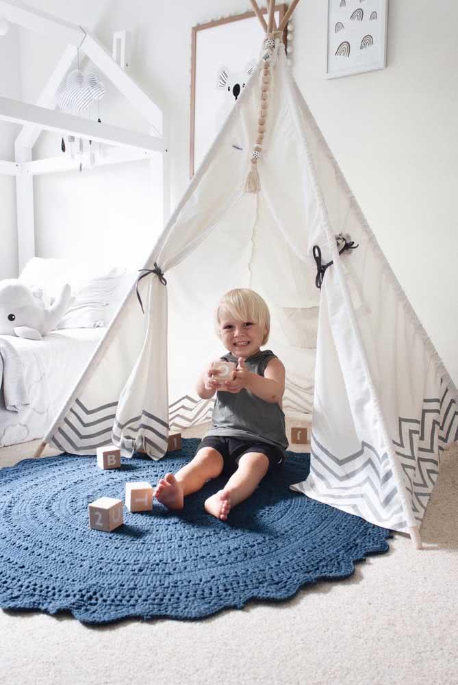 Já o quarto de bebê decorado em branco e preto recebeu um tapete de crochê azul escuro