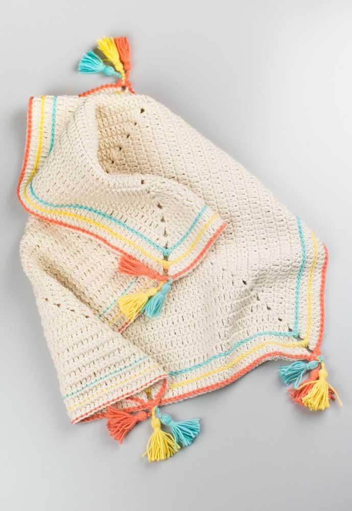 Tapete de crochê em barbante para quarto de bebê. O diferencial aqui está nas linhas coloridas e nos pompons