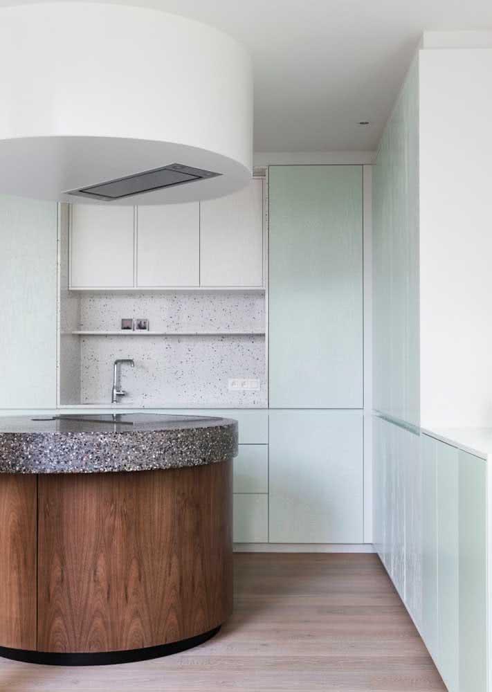 Uma bancada central com formato diferenciado e oval em uma cozinha em L verde clara