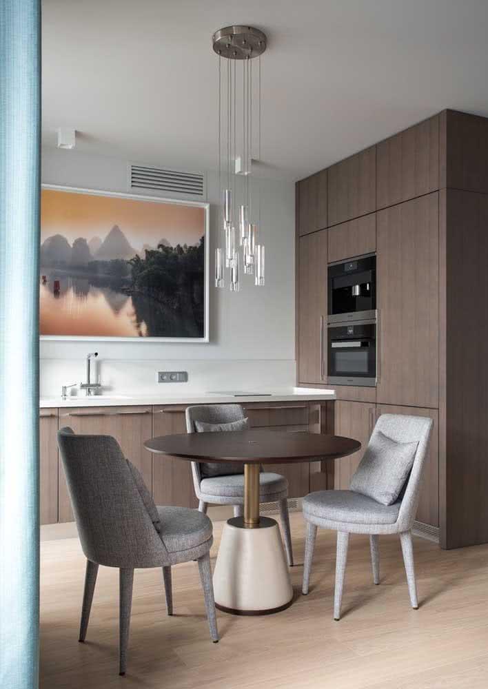 Lustre pendente e mesa redonda em uma cozinha em L com foco nos tons de madeira. Diferencial para o quadro na parede da bancada.
