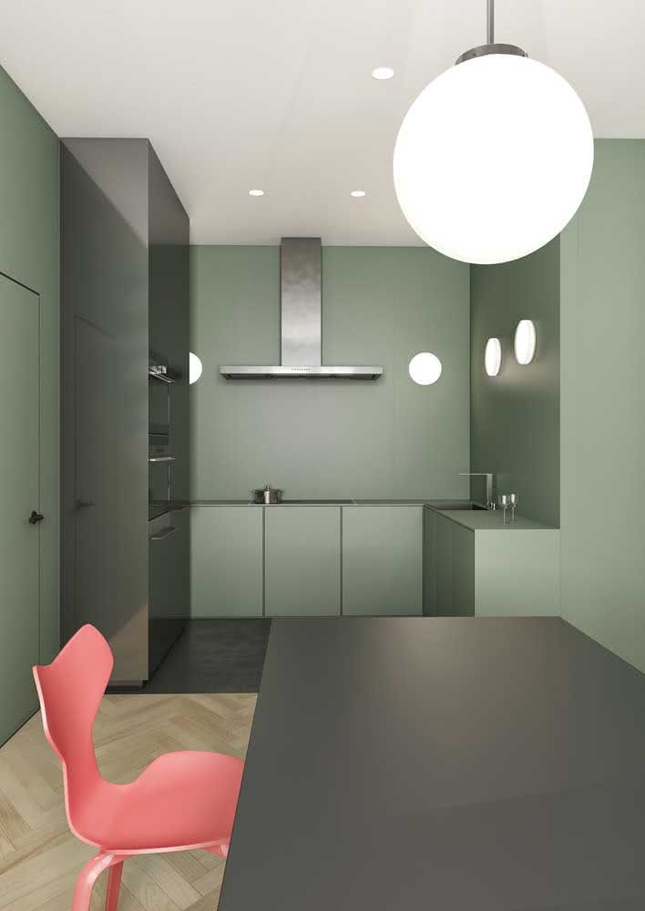 Cozinha verde minimalista em L e armários sem puxadores.