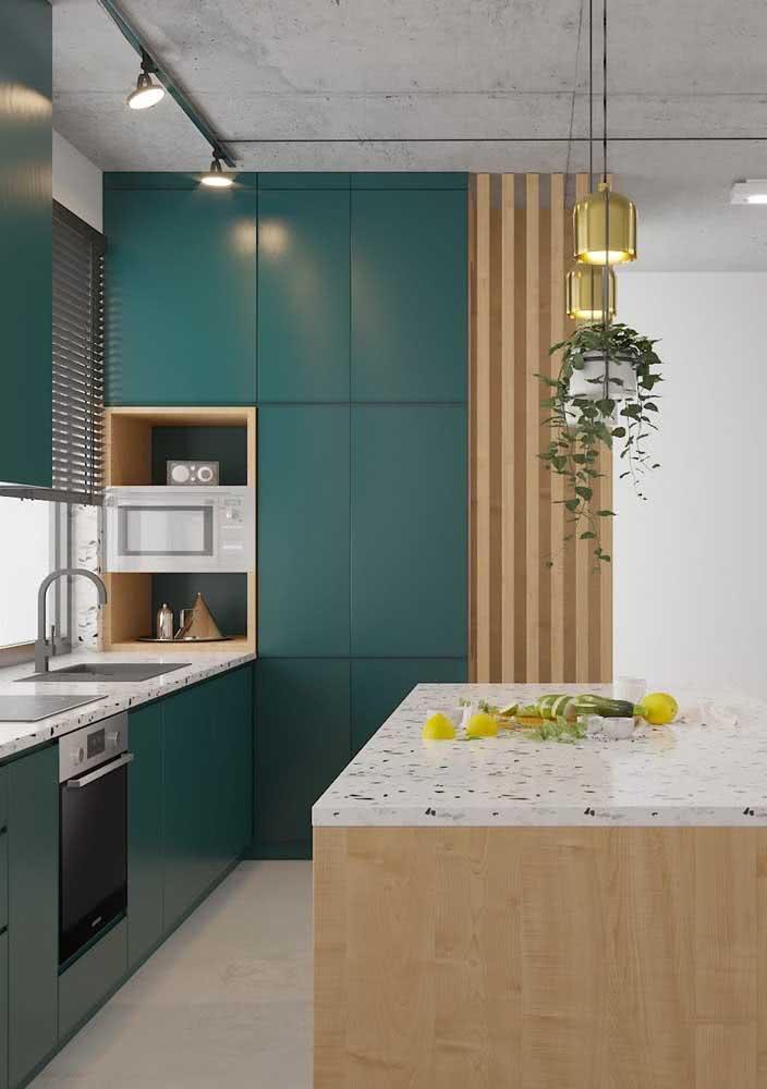 Cozinha planejada com armários verde água, lustres pendentes dourados e madeira clara