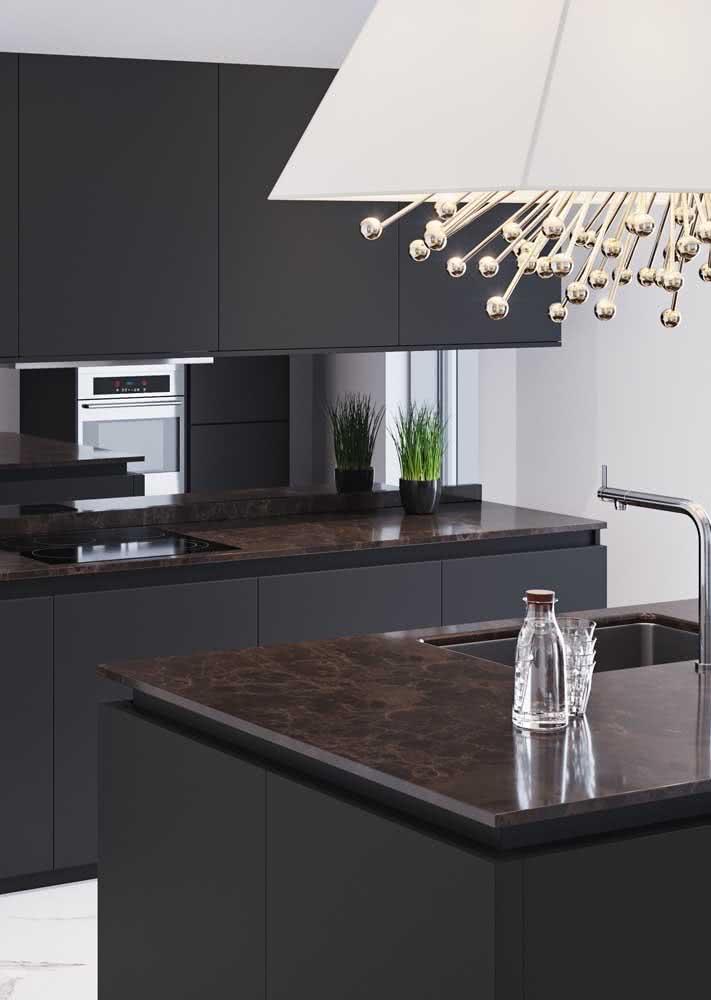 Um projeto sóbrio e elegante com armários pretos e pedra marrom nas bancadas