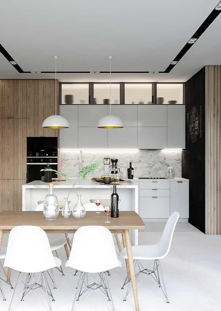 Cozinha branca com iluminação na bancada e muito espaço para curtir com as pessoas queridas.