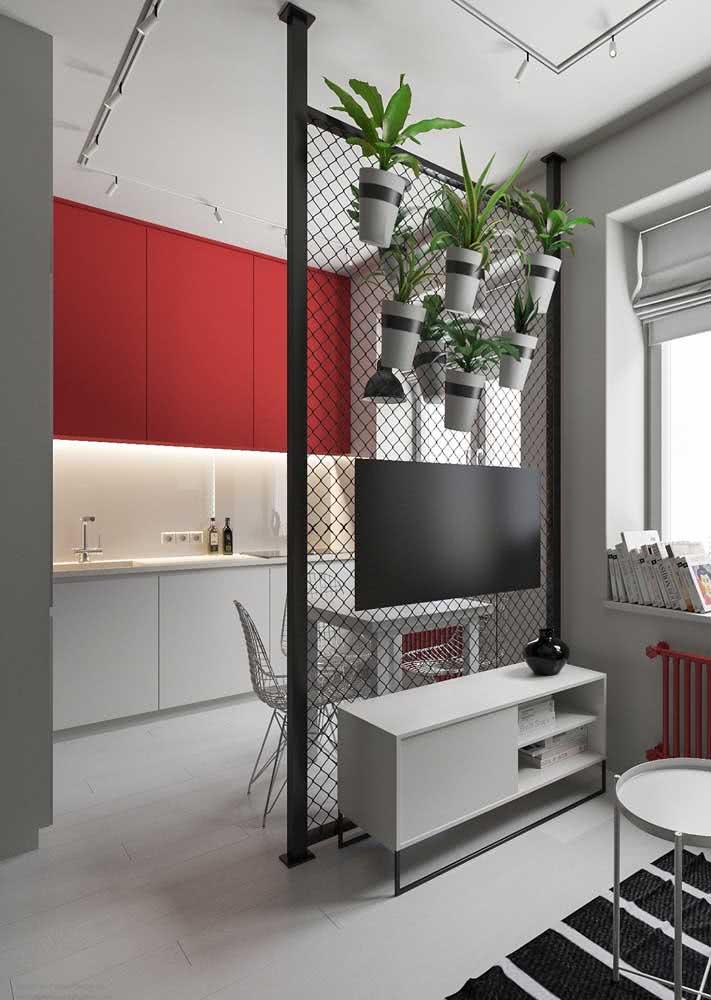 Cozinha vermelha e cinza minimalista e com pequena mesa para refeições rápidas.