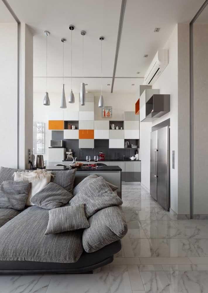 Pé-direito alto e uma cozinha que brinca com as cores através dos módulos do armário.