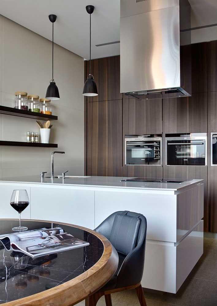 Cozinha planejada incrível com armários com tom escuro de madeira, fornos embutidos e uma linda pia com cooktop e coifa em aço inox.