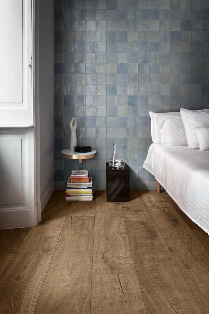 Porcelanato amadeirado no piso e pastilhas cerâmicas na parede da cama