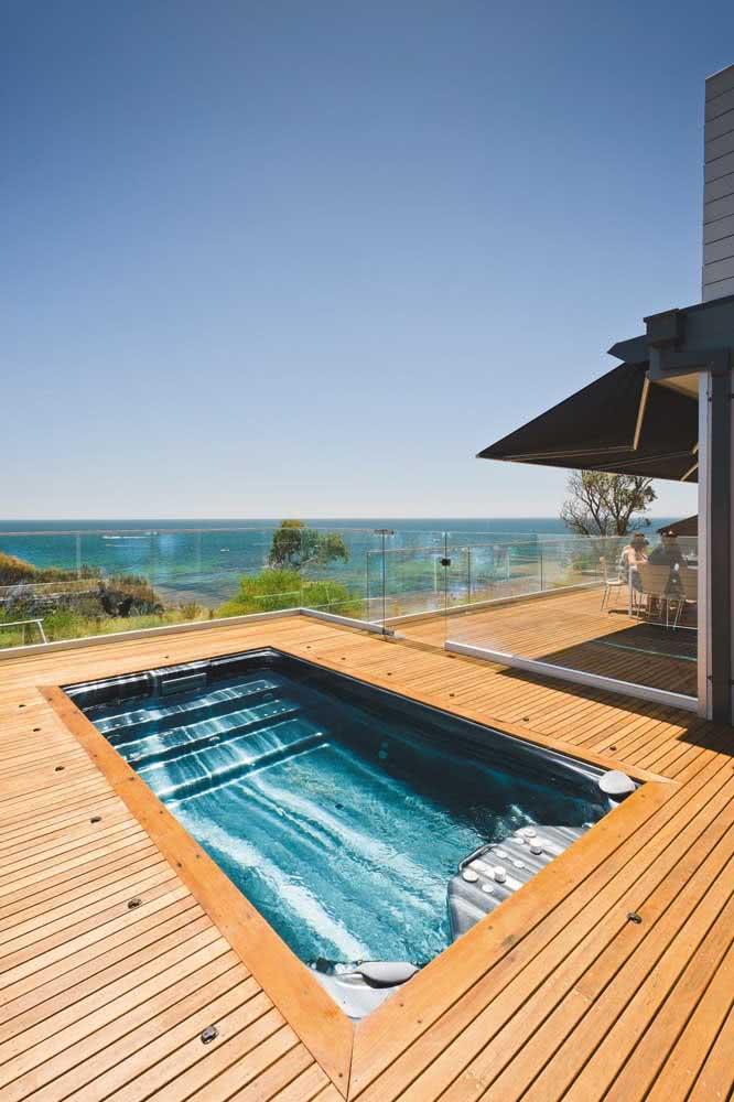O deck de madeira ajuda a deixar a área da piscina com hidro mais acolhedora e convidativa