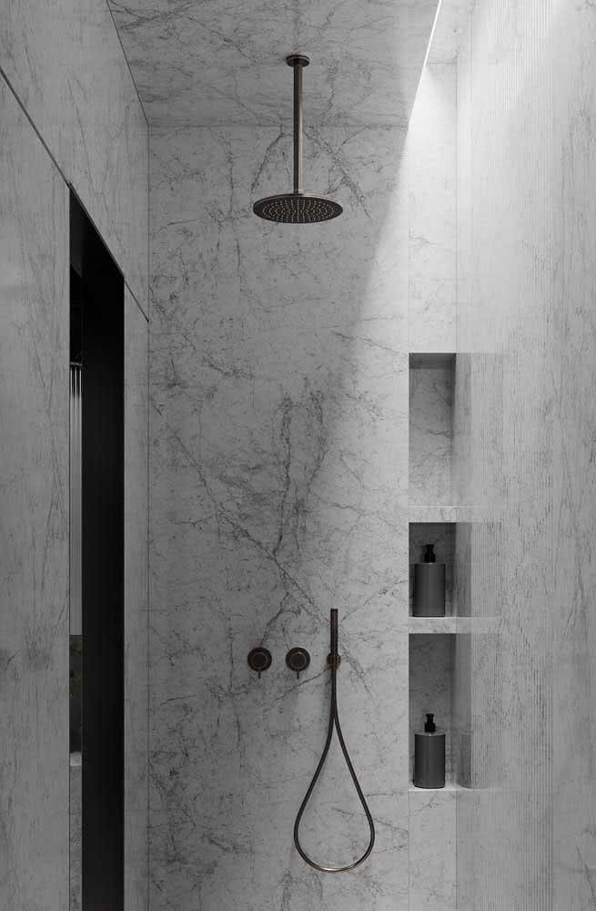 Banheiro com revestimento de mármore e chuveiro de teto