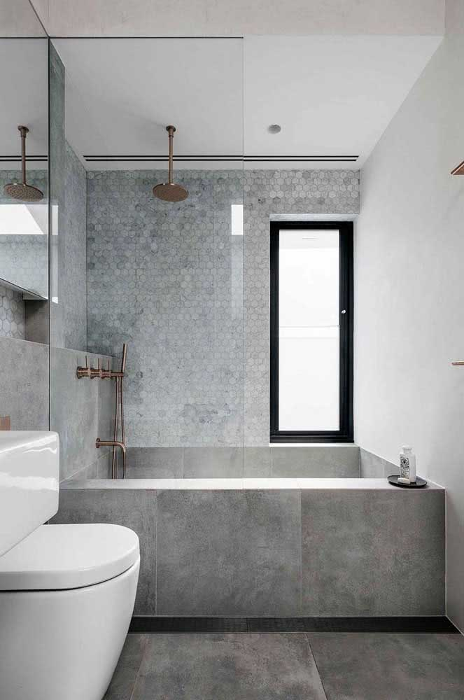 Chuveiro de teto dourado em destaque no banheiro moderno