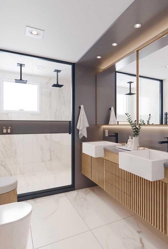 O banheiro amplo apostou em uma dupla de chuveiros de teto com tubo
